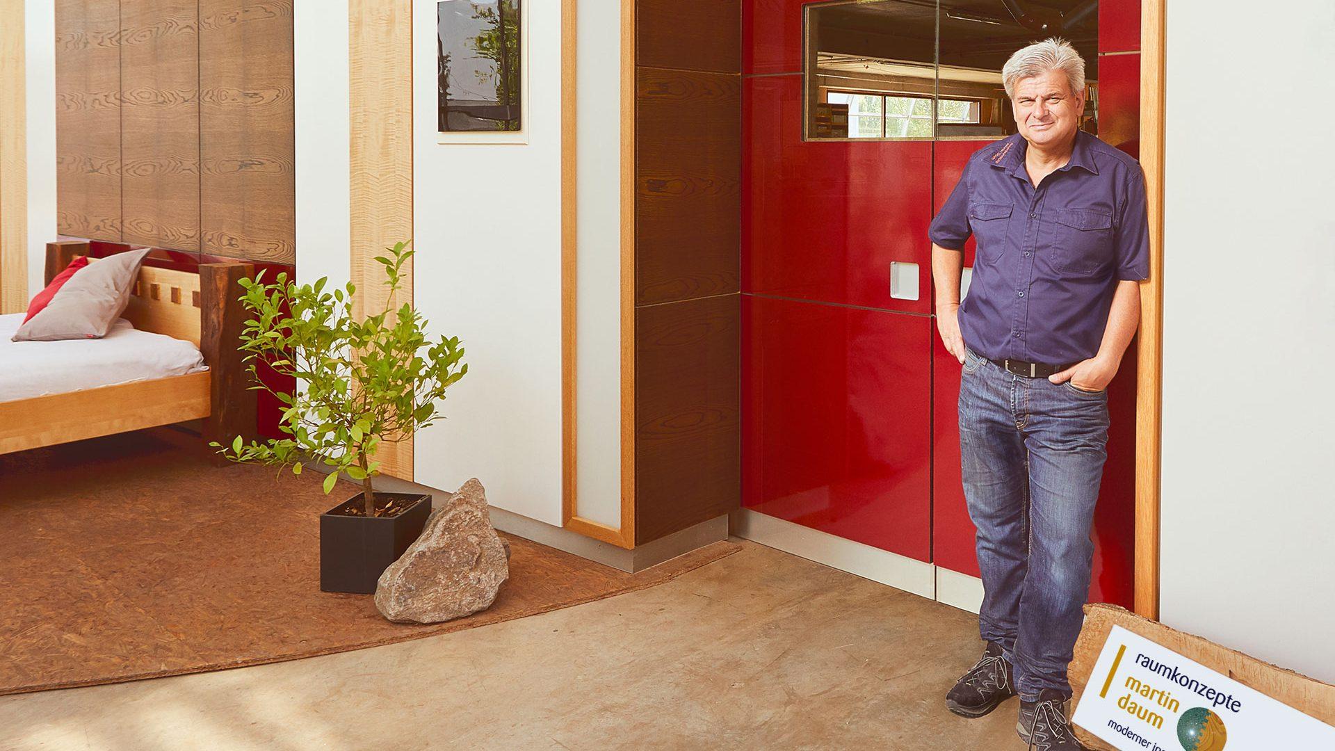 Herr Daum steht vor seiner Werkstatt von Raumkonzepte Daum